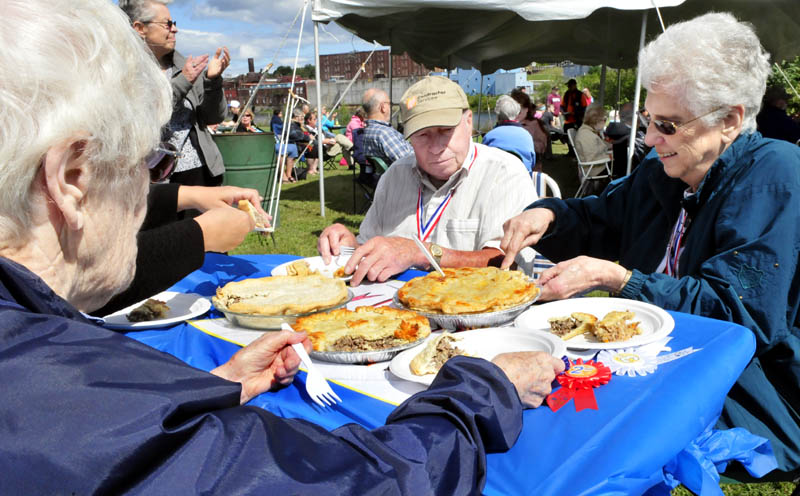 Judges for the popular French dish tourtiere begin to sample entries in the best pie contest during the Franco-American Family Festival in Waterville today. From left are Cecile Vigue, Reginald Dumont and Rita Hikel. Janette White won first place, followed by Karen Rancourt-Thomas and Sandra Leighton.