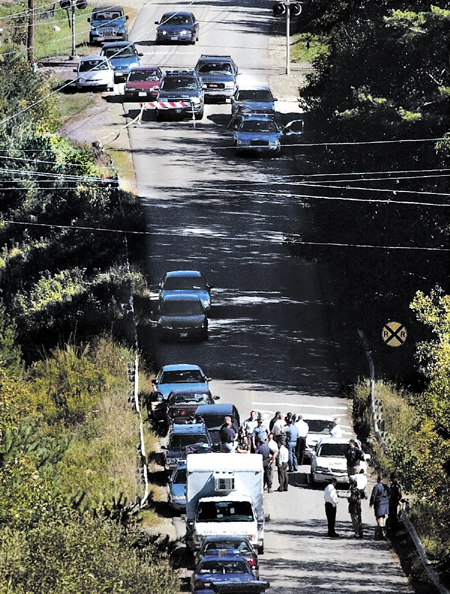 State Police investigators, Waterville and Oakland police assembled at the base of the Rice Rips Road in Oakland on Sept. 17, 2003, to investigate the discovery of Colby College student Dawn M. Rossignol, who was found found dead that morning.