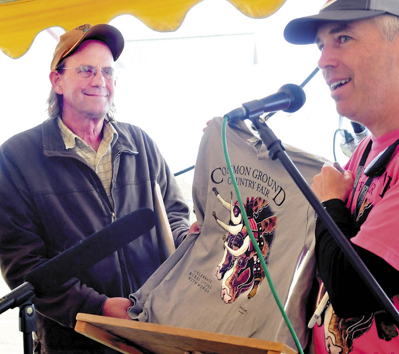Common Ground Country Fair Director Jim Ahearne, right, present this years fair T-shirt to keynote speaker George Siemon, cofounder of the Organic Valley cooperative, following his talk at the Unity fair today.