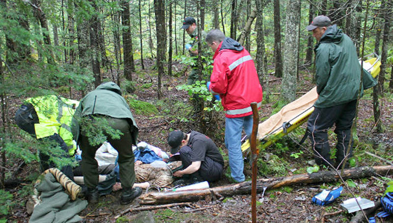 Maine Warden Service Chaplain Kate Braestrup crouches on the ground next to 86-year-old Arthur Wakeman after he was found about 1.2 miles from his Benton home Friday.