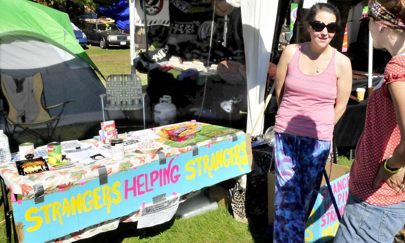 Andie Burke, left, speaks with Casey Joudrey at the Strangers Helping Strangers booth during the Great North Fest in Norridgewock today. The Massachusetts nonprofit attends concerts and festivals, collecting donated or leftover, nonperishable food and hygiene products, which it donates to pantries.