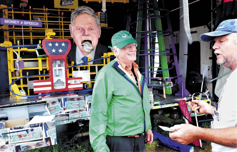 Ben Cohen, left, cofounder of Ben and Jerry's Ice Cream, speaks with George Stanley at his booth, featuring the Amend-O-Matic StampMobile, at the Common Ground Country Fair in Unity today.