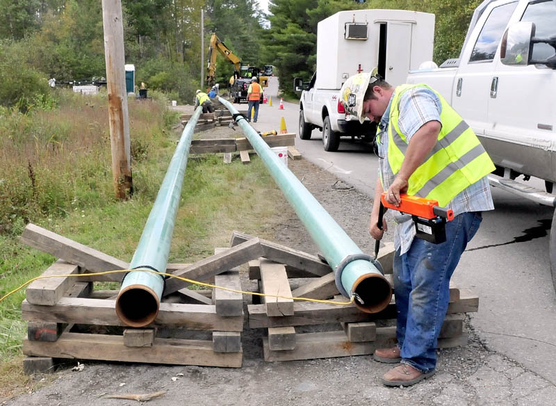 Jeremy Clubbs, of sub-contractor U.S. Pipelines, works on preparing to install gas pipeline sections outside Sappi Fine Paper on Wednesday in Skowhegan off the Varney Road. The spur will connect the mill to a main line running through Fairfield.