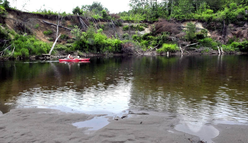 Bill Moloney paddles his kayak past a section of the Sandy River in Farmington in June where the banks eroded near the Whittier Road, top.