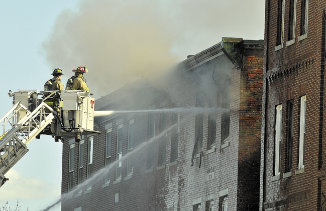 Waterville firefighters battle a fire at 18 Main St. on May 3. That fire has prompted the City Council to consider on Tuesday mandating sprinkler systems, inspections and other safety measures for downtown buildings.