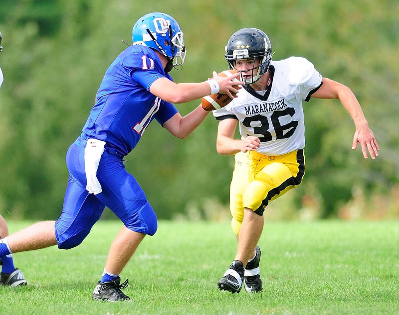 Oak Hill quarterback Parker Asselin tries to run away from Maranacook defensive end Simon Davis but got sacked on the play during a game on Saturday in Wales.