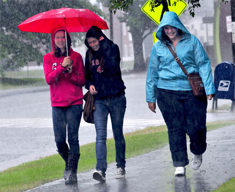 University of Maine at Farmington students Kristen Tarr, Anna Dowling and Jen Perry exit the student union in the rain today.