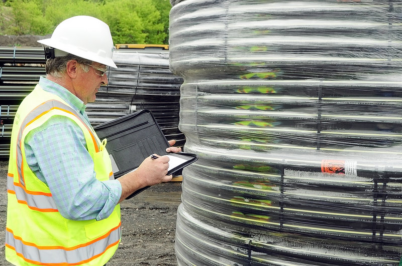 Bruce Madore, director of engineering and construction, looks over natural gas pipes in the Summit Natural Gas of Maine yard in Augusta.