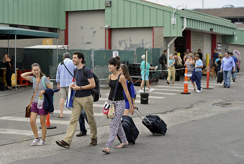 Travelers head to the Peaks Island Ferry Saturday. Behind them is the Casco Bay Ferry Terminal in Portland. Groundbreaking for terminal upgrades takes place Wednesday.
