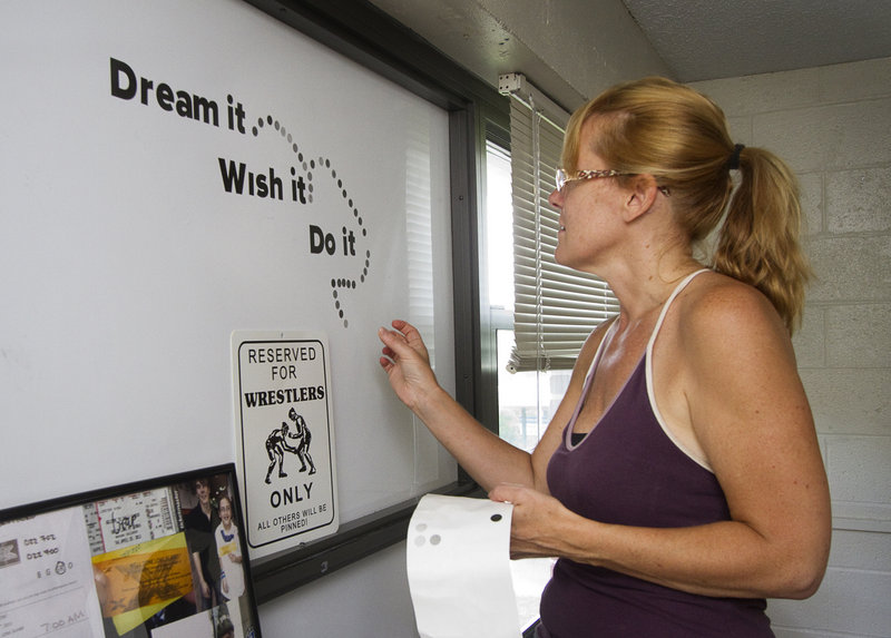 "Linda Bonina of Hudson, Mass., decorates the white board in her son Vinny's USM dorm room with some words of inspiration Sunday. ""I found this and want him to read this every day,"" she said of the quotation."
