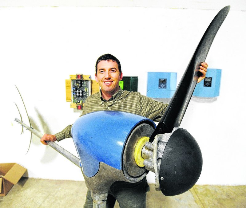 Ben Polito, president of Pika Energy in Westbrook, holds one of three blades on a personal-size wind turbine. Polito said he appreciates the mentoring he gets from investors.