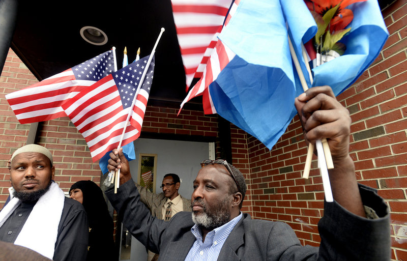 Mohamud Barre, Executive Director of the Somali Culture and Development Association of Maine, holds American and Somalian flags as members of the local Somali community speak with the press after a meeting with Congresswoman Chellie Pingree at the Islamic Society of Portland on Tuesday, Sept. 24, 2013.