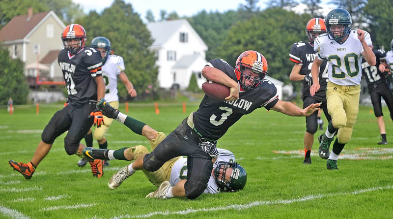 Winslow High School's Dylan Hapworth, 3, breaks away from Mount Desert ISland High School's Dakota Stewart, 10, in Winslow on Saturday. Winslow defeated MDI 49-18.