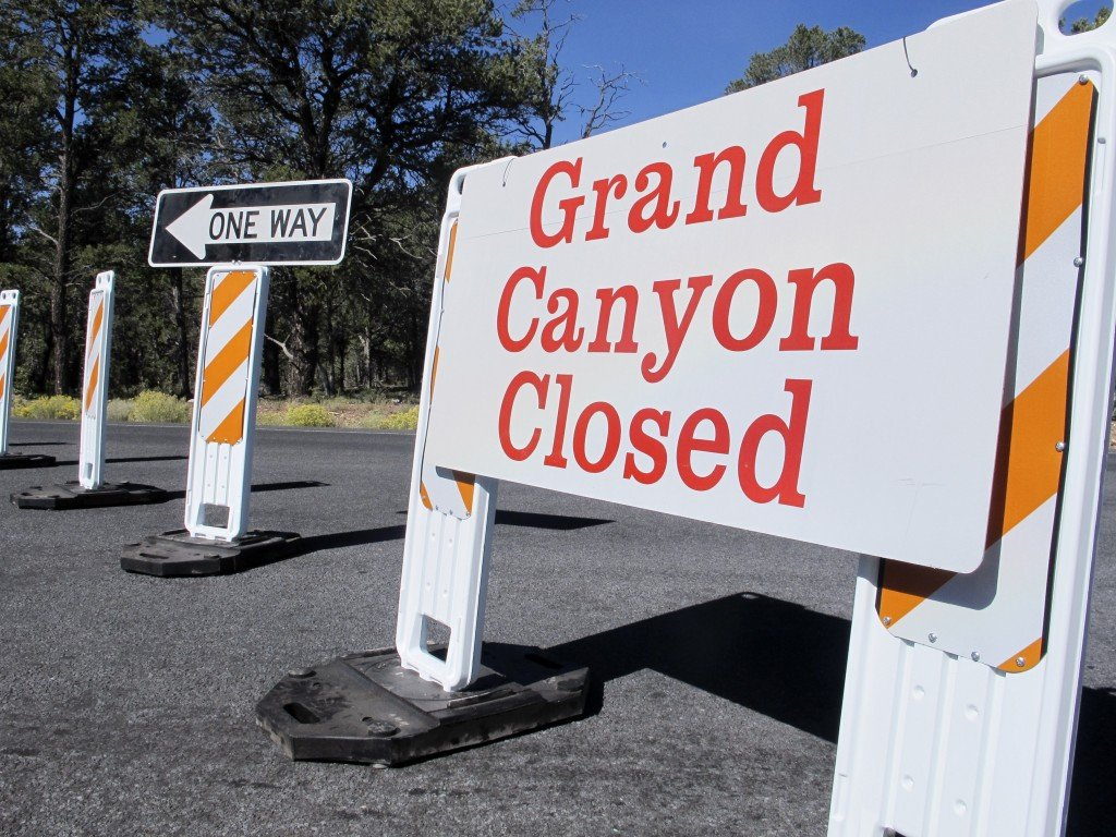 This Oct. 3, 2013, photo shows a sign at the south entrance to Grand Canyon National Park, Ariz. October is normally a peak month for tourism in many parts of the West.