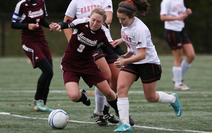 Madison Bumann, left, of Monmouth Academy stumbles as she fights for the ball with North Yarmouth Academy's Jennifer Machin during their Western Class C girls' soccer prelim Friday afternoon in Yarmouth. Monmouth won in overtime, 1-0.
