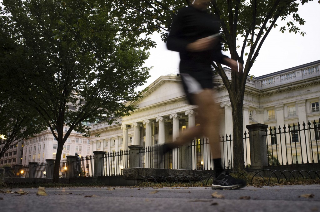 A jogger on an early morning run passes the U.S Treasury Building in Washington, Wednesday, Oct. 16, 2013, a day before the stalemate in Congress over the budget could cause the government to reach its borrowing limit.