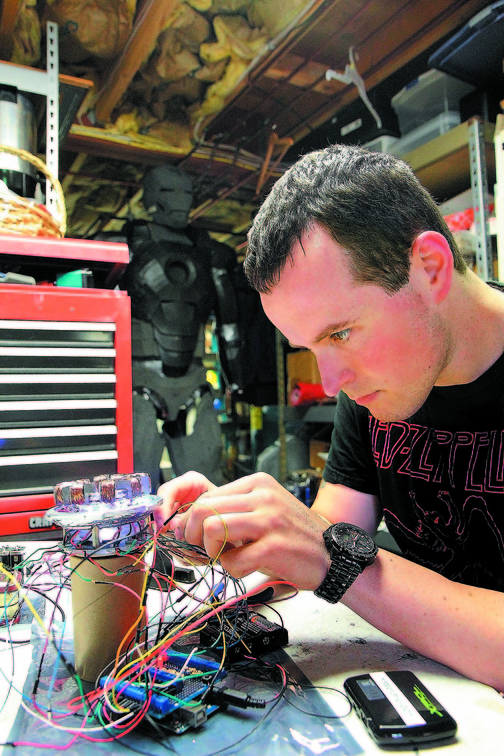 Invention: Oakland resident Thomas Lemieux works on one of the electronic components of his Iron Man suit during the summer.