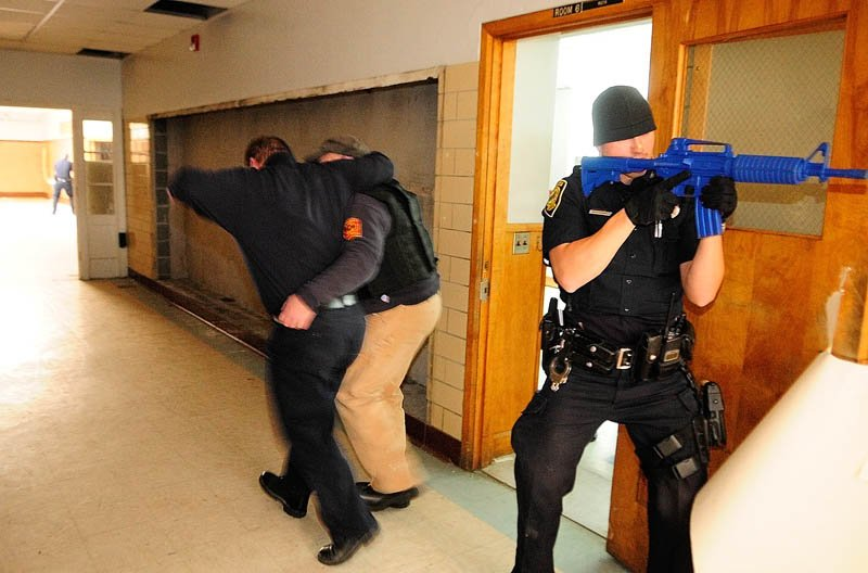 Augusta firefighter/paramedic Bill Lord, left, playing a victim, is helped down a hallway by Augusta firefighter/paramedic Randy Gordon as Augusta police officer Nico Hample provides cover, during a training exercise on Thursday at the former Hodgkins middle school in Augusta.