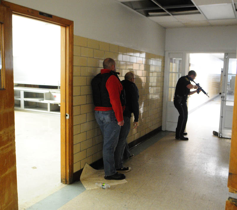 Augusta firefighter/paramedics Scott Sirois, left, and Rich Beaudoin stay low and close to the wall as they follow Augusta police patrolman Ben Murtiff down a hallway during a simulated school shooting incident Friday at the former Hodgkins Middle School in Augusta.