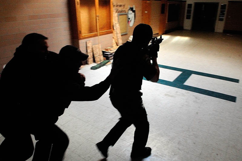 Augusta firefighter/paramedic Steve Almquist, left, playing a victim, gets carried out by firefighter/paramedic Shawn Stevens, as they follow Augusta police officer Nico Hample down a hallway during a training exercise Friday at the former Hodgkins middle school in Augusta.