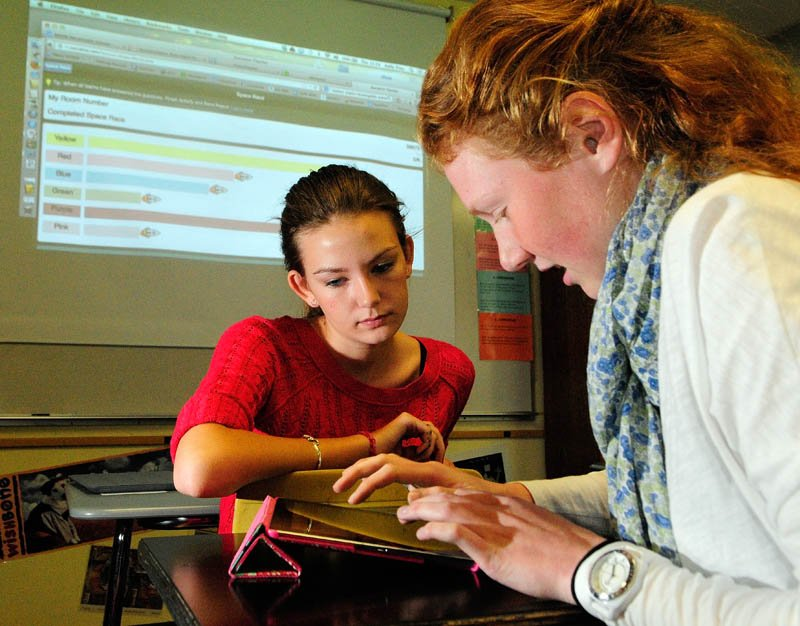 Jaime Sechrist, left, and Melissa Garand work as a team to answer questions on an iPad while a screen charts their progress against other teams during teacher Kelly Frey's Spanish class on Thursday at Maranacook Community High School in Readfield.