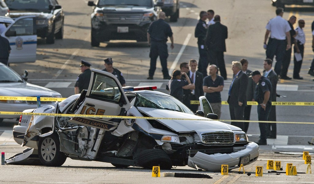 A damaged Capitol Hill police care is surrounded by crime scene tape after a car chase and shooting on Capitol Hill in Washington, Thursday, Oct. 3, 2013. A woman driving a black Infiniti with a young child inside tried to ram through a White House barricade Thursday, then led police on a chase that ended in gunfire outside the Capitol, witnesses and officials said.