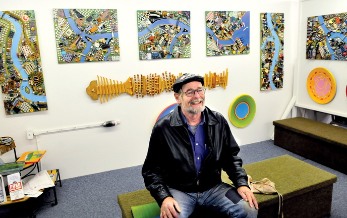 """COLORFUL FELLOW: Artist Wally Warren speaks about his art including """"City of Dreams"""" behind him at the Central Maine Artists Gallery in Skowhegan."""