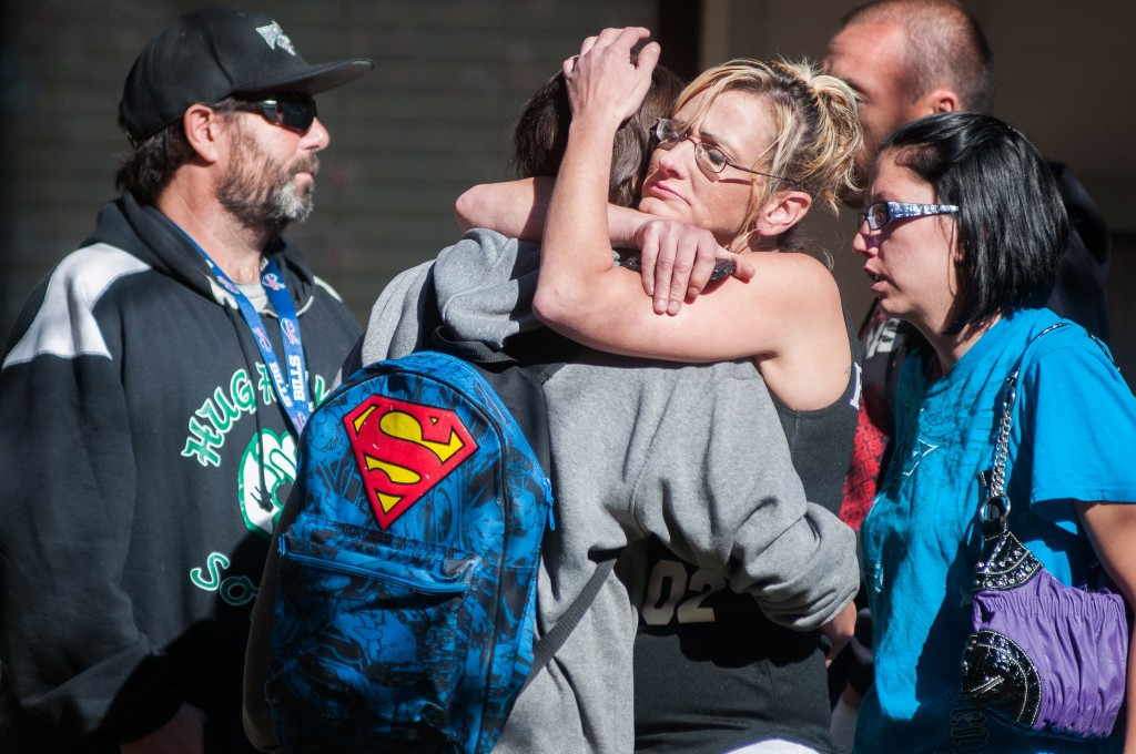 A Sparks Middle School student, back to camera, cries with family members after being released from an evacuation center Monday in Sparks Nev., after a shooting at Sparks Middle School.