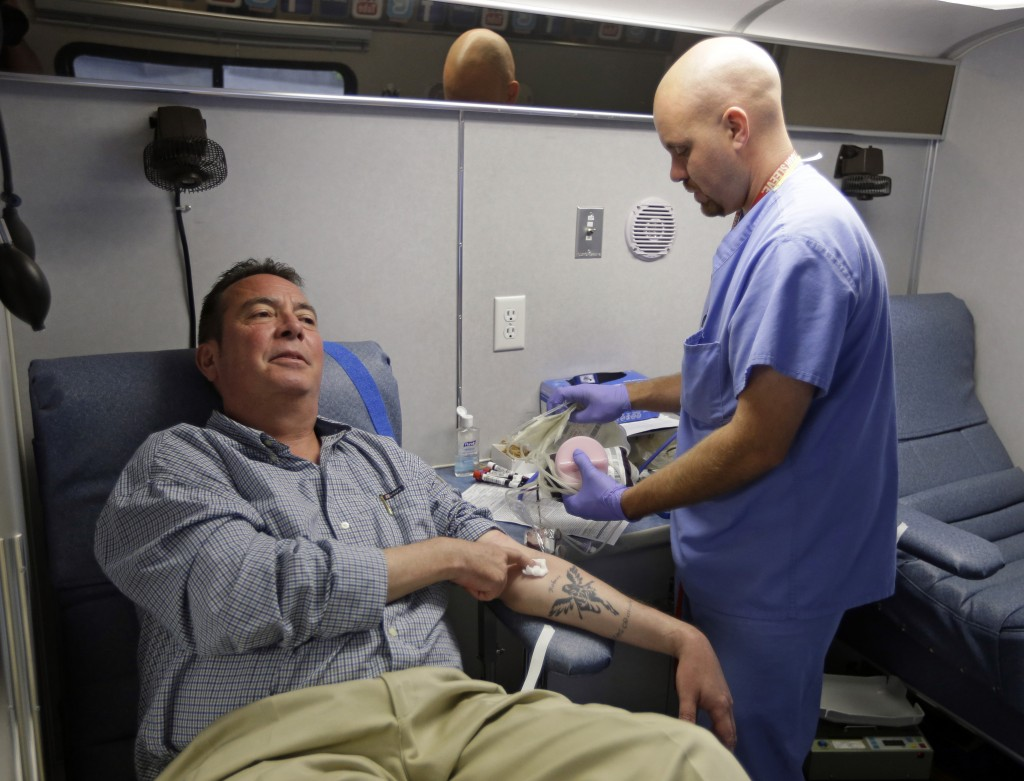 Technician Greg Snyder, right, finishes up a blood draw from Chris Page after he donated blood in an Indiana Blood Center Bloodmobile in Indianapolis recently. The Indiana Blood Center announced in June 2013 that it would reduce its mobile operations, close a donor center and cut other costs because demand from hospitals had fallen 24 percent from the previous year.