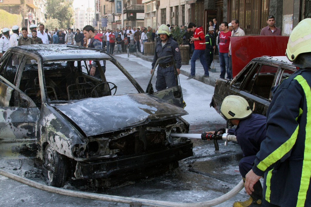 Firefighters extinguish a burning vehicle after two mortar rounds struck the Abu Roumaneh area in Damascus, Syria, Saturday, Oct. 12, 2013. Syriaís state news agency said two mortar rounds struck an upscale neighborhood in the Syrian capital of Damascus, killing at least one child and injuring a dozen people.