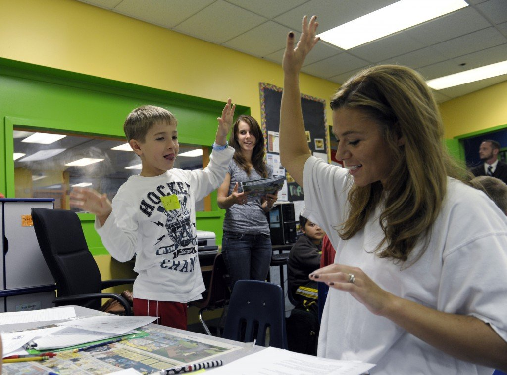 Josh Gillespie, 8, high-fives parent helper Shannon Morgan, right, after they solved a math problem during a lesson at the Andrews Air Force Base, Md., homeschooling cooperative with a math class teacher Jennifer Whittaker, center.