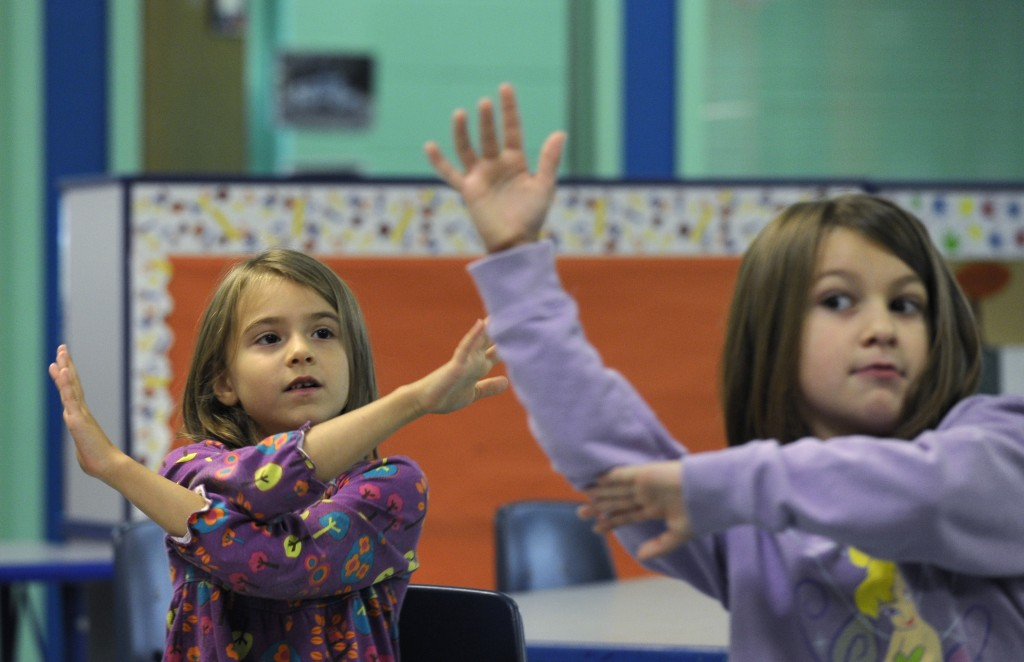 In this photo taken Oct. 9, 2013, Grace Whittaker, left, and Andria Kirkendall, right, learn sign language during a lesson at a homeschooling co-operative at Andrews Air Force Base Md. A growing number of military parents have embraced homeschooling, seeking to put an end to the age-old tradition for military kids of switching schools.