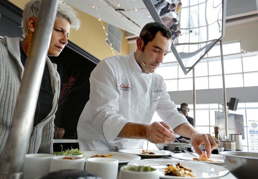 Chef Chris Long of Natalie's at Camden Harbour Inn plates his winning dish of butter-poached Maine lobster during the Lobster Chef competition at Portland's Ocean Gateway on Thursday, as emcee Michele Ragussis looks on.