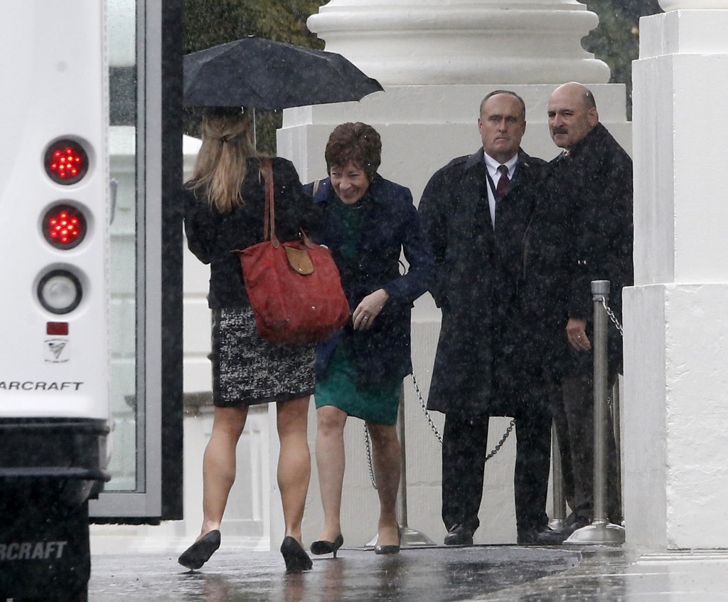 Sen. Susan Collins, R-Maine, walks in the rain back to her bus at the North Portico of the White House in Washington on Friday after she and Republican senators met with President Barack Obama regarding the government shutdown and debt ceiling.