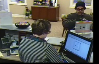 This image taken from a surveillance video shows a man robbing a teller at the Ocean Communities Federal Credit Union in Sanford on Saturday.