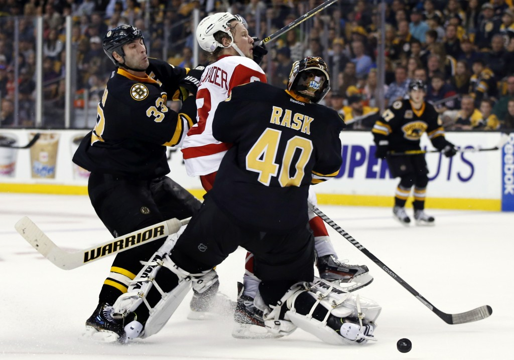 Detroit Red Wings left wing Justin Abdelkader (8) is checked by Boston Bruins defenseman Zdeno Chara (33) and goalie Tuukka Rask (40) in front of the crease in the third period of an NHL hockey game in Boston, Monday, Oct. 14, 2013. The Red Wings won 3-2.