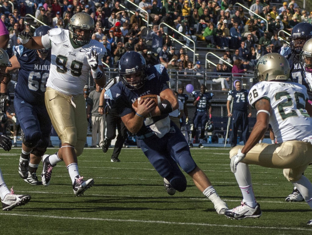 Maine quarterback Marcus Wasilewski carries the ball inside the 5-yard line past William and Mary players Tyler Clayter, 99, and Ryan Smith in the first half of Saturday's game at Orono. UMaine improved to 6-1 with a 34-20 win.