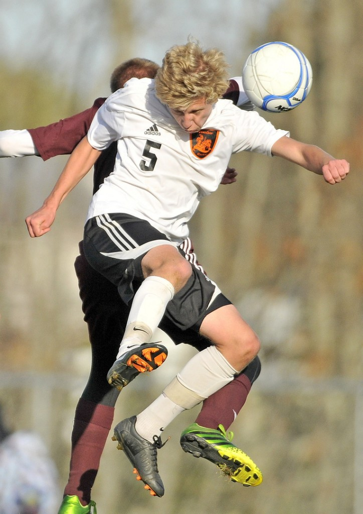 WIN IT: Winslow High School's Evan Clark (5) battles for the ball with Foxcroft Academy's Dylan Harmon-Weeks in the second half of the Black Raiders' 2-1 win over in an Eastern B quarterfinal Wednesday in Winslow.