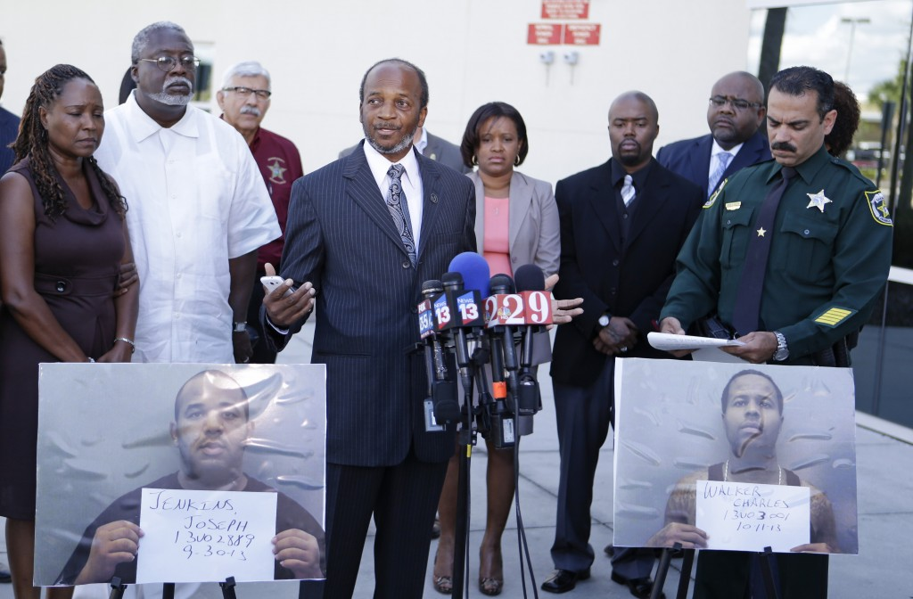 Lillie Danzy, front left, mother of escaped inmate Charles Walker, with her husband Jeff Danzy, second from left, and family supporters and members of the Orange County Sheriff's Office listen as Henry Pearson, center, uncle of escaped inmate Joseph Jenkins, makes a plea for his nephew to turn himself in to authorities during a news conference in Orlando, Fla., Saturday, Oct. 19, 2013. Joseph Jenkins, photo front left, and Charles Walker, photo front right, two convicted killers freed by bogus paperwork, are at large.