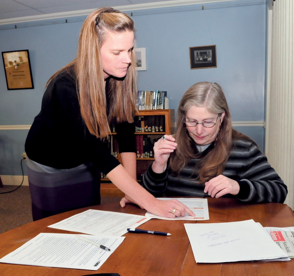 Health navigator Cheryl Leonard, left, assists Amy Goldstein with Affordable Health Care paperwork after attempts to work on the program website failed at the Winslow Public Library on Monday.