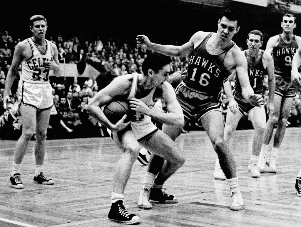 Boston Celtics' Bill Sharman holds the ball as St. Louis Hawks' Cliff Hagan defends, during an NBA Finals basketball game in Boston on March 30, 1958. Sharman, the Hall of Famer who won NBA titles as a player for the Boston Celtics and as a coach for the Los Angeles Lakers, has died. He was 87.
