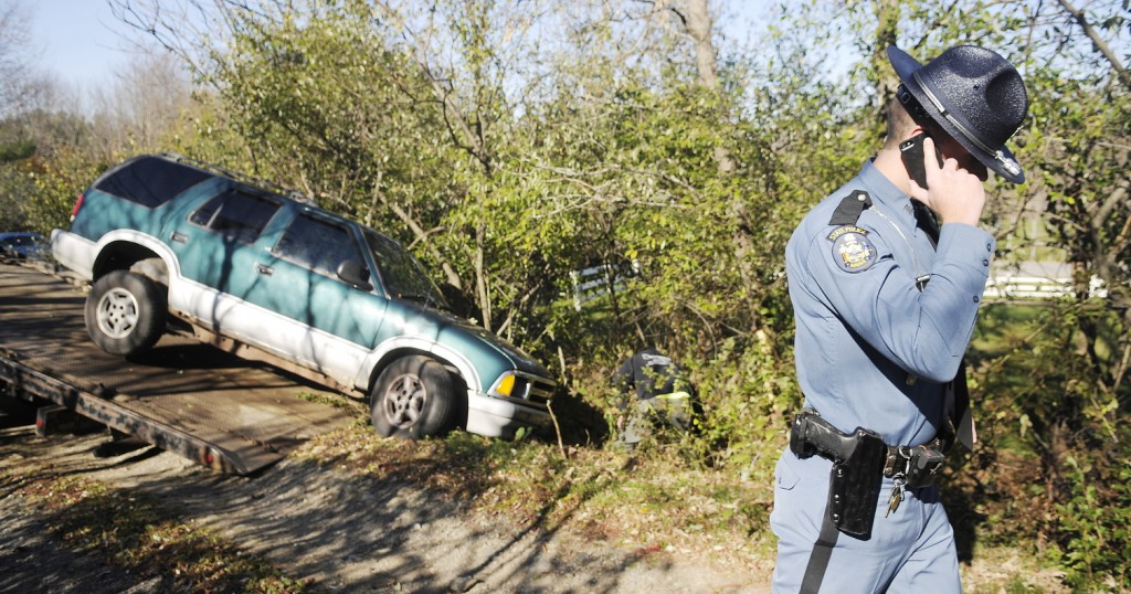 FOOT CHASE: A state trooper speaks on the phone Tuesday morning after a man fled from police on Route 9 in Chelsea. Troopers pursued the driver of the sport utility vehicle for about four hours.