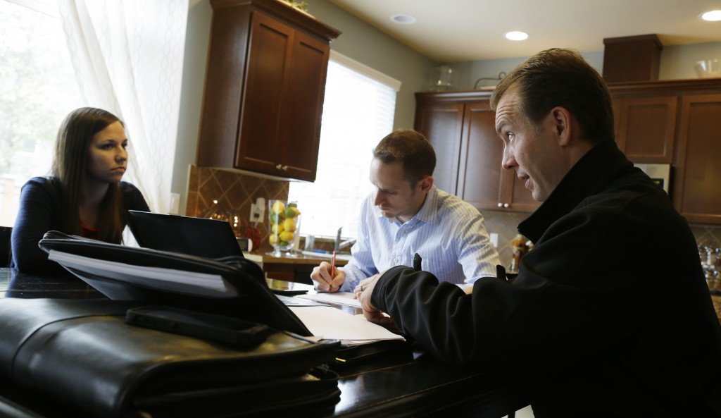 The Associated Press Insurance broker Jeff Lindstrom, right, meets with Brandi and Darren Litchfield to discuss health insurance plan options, at their home in the Seattle suburb of Bothell, Wash. Darren works for a startup company that doesn't yet offer an employee insurance plan, so they invited Lindstrom to outline the options of different healthcare plans that he offers as a broker.