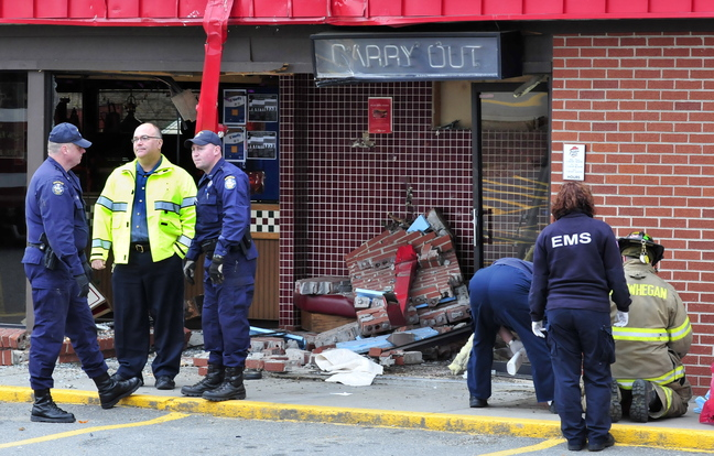 AFTERMATH: Firefighters, state police and Skowhegan Police Chief Ted Blais, second from left, investigate the scene where a truck loaded with wood crashed into the Pizza Hut restaurant in Skowhegan on Monday.