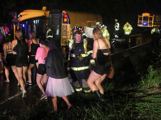 Passengers walk past the bus that overturned after colliding with a car carrier truck in Bear, Del., Thursday evening.