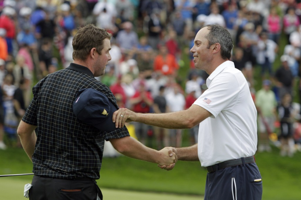 United States team player Matt Kuchar, right, shakes hands with International team player Marc Leishman, of Australia, on the 18th green during the single matches at the Presidents Cup golf tournament at Muirfield Village Golf Club Sunday, Oct. 6, 2013, in Dublin, Ohio.