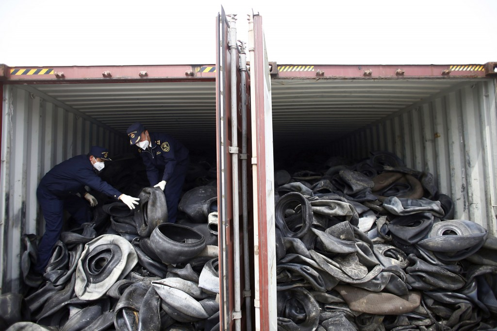 Chinese customs officials check a container of illegally imported used tires in Shanghai.