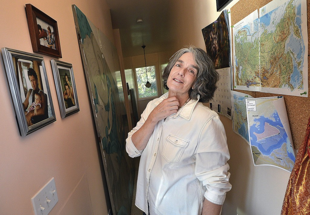 Maggy Willcox, wife of Peter Willcox, captain of the Greenpeace vessel Arctic Sunrise, stands near photos of her husband with his children on a wall in his boyhood home, in Norwalk, Conn. Willcox spoke with her husband Monday for the first time since he was arrested in September during a protest in the Arctic.