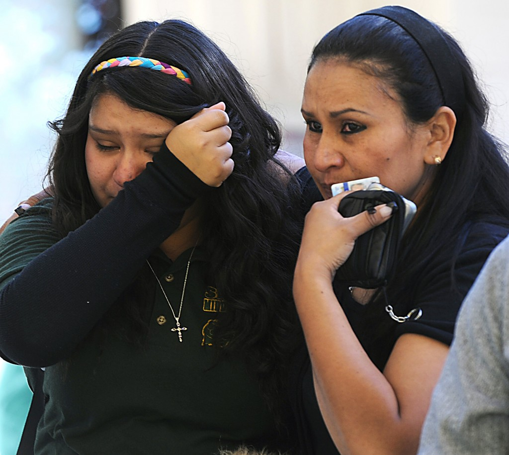 A tearful Michelle Hernandez, left, is led away from Agnes Risley Elementary School following a shooting at Sparks Middle School in Sparks, Nev. on Monday. Police on Tuesday said the boy who opened fire brought the weapon from his home.