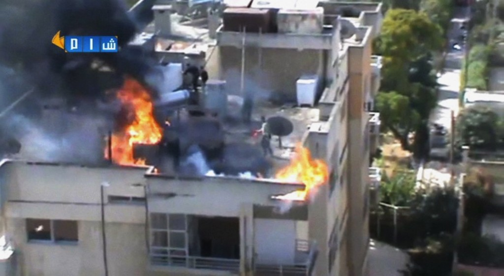 In this image taken from video obtained from the Shaam News Network, which has been authenticated based on its contents and other AP reporting, people try to extinguish a fire on the roof of a building, allegedly caused by shelling in Homs, Syria, on Thursday. President Bashar Assad's government met a key deadline in an ambitious plan to eliminate Syria's entire chemical weapons stockpile by mid-2014 and avoid international military action.